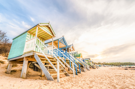 beach huts: long line of colorful beach huts at sunset