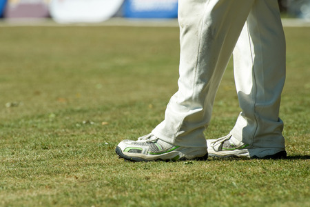cricketer: feet of a cricketer in traditional white trousers