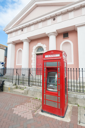 telephone box: Vintage red telephone box converted into a ATM cash machine in Weymouth UK  June 13 2013 Editorial