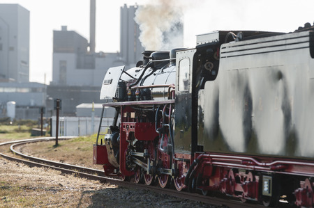 railway transportation: Dungeness UK  May 3 2014: The vintage coal powered Black Prince steam train arriving at a modern nuclear power station in Kent UK