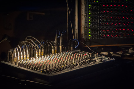 gig: spotlight illuminating a soundboard mixer at a live music event
