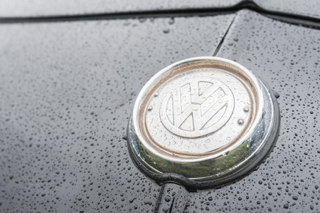 vw: Rushmoor, UK - April 3, 2015: Closeup of a vintage VW vehicle badge insignia covered with raindrops. Editorial