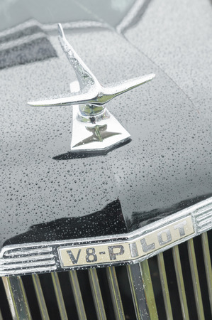 v8: Rushmoor, UK - April 3, 2015: Closeup of a vintage V8 Ford Pilot vehicle hood ornament covered in raindrops.
