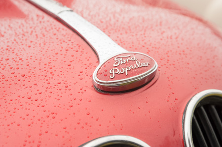 Rushmoor, UK - April 3, 2015: Closeup of a vintage Ford Popular vehicle badge covered in raindrops.