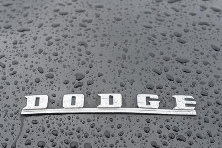 motor cars: Rushmoor, UK - April 3, 2015: Closeup of a raindrop covered hood badge on a Dodge muscle car. Editorial