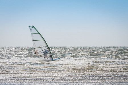 windsurfers: windsurfer riding the waves in an empty sea