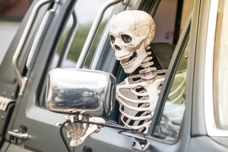 scary human skeleton figure driving a truck