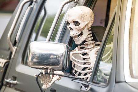 halloween skeleton: scary human skeleton figure driving a truck