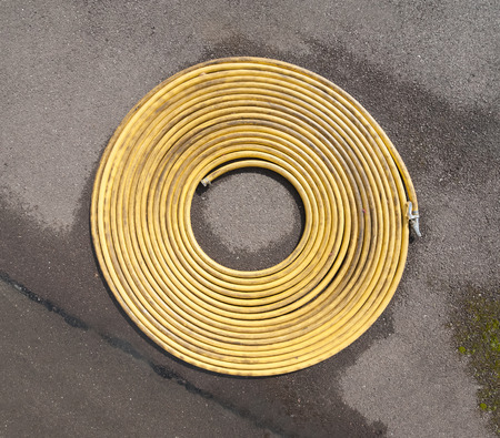 hosepipe: coiled water hosepipe on a damp concrete surface