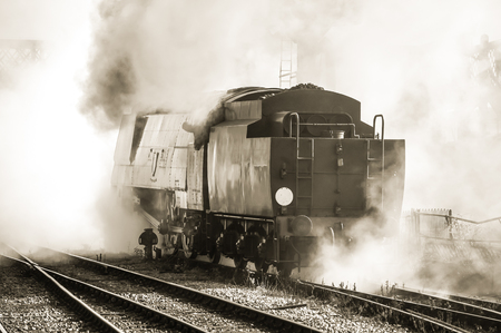 railway transportations: sepia toned vintage locomotive in a cloud of steam Stock Photo