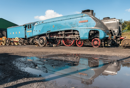 Ropley, UK - 19 September, 2015: Vintage steam locomotive LNER Bittern and its reflection at the Mid-Hants Watercress railway station of Ropley, UK