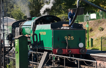 Ropley, UK - 19 September, 2015: An engineer filling the water tender of a vintage steam locomotive at the Mid-Hants Watercress railway station of Ropley, UK