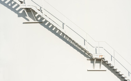 metallic stairs: metallic staircase floating on an off-white wall background