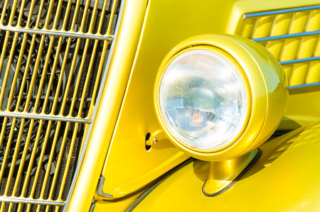 grille': bright yellow vintage vehicle grille and headlight closeup Stock Photo