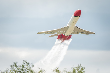 oil spill: Farnborough, UK - July 14, 2016: Low-level demonstration of a Boeing 727 oil spill response aircraft operated by OSRL at an aviation trade event.
