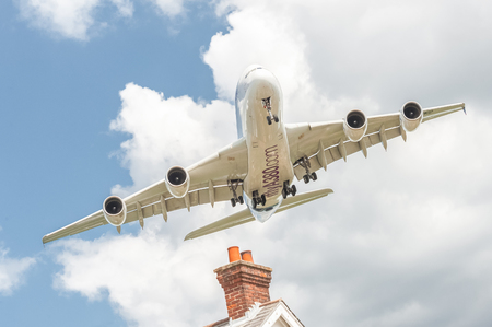 undercarriage: Farnborough, UK - July 14, 2016: Airbus A380 on a low banked approach before landing at an aviation trade event Editorial