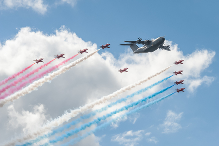red arrows: Farnborough, UK - July 17, 2016: Red Arrows formation flying team and an Airbus A400 transporter in the skies over Farnborough, UK Editorial