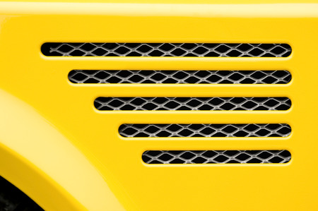 auto engine grill closeup on a bright yellow vehicle Stock Photo