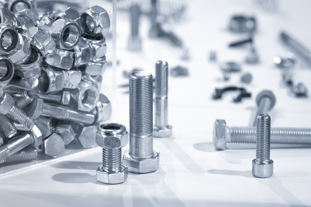 metal fastener: blue toned industrial nuts and bolts close-up Stock Photo