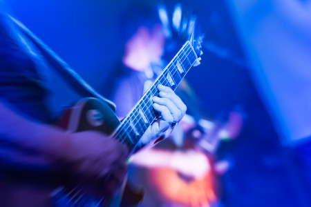 musician playing an electric guitar under blue stage lighting 写真素材