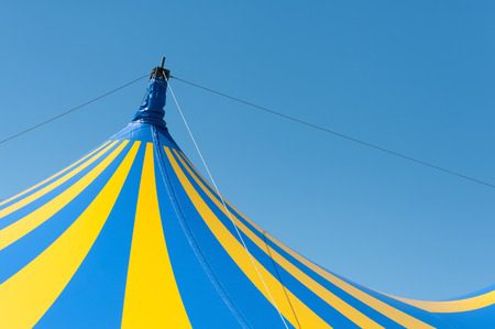showbusiness: large yellow and blue circus big top canvas against a clear blue sky
