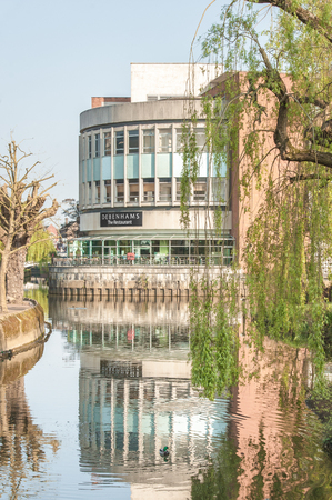 Guildford, UK - April 6, 2017: Early morning reflections of the Debenhams department store restaurant on the banks of the River Wey near Guildford, UK