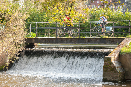 weir: two people cycling on a bridge over a small waterfall