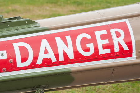 closeup of a danger sign on the fuselage of a vintage helicopter
