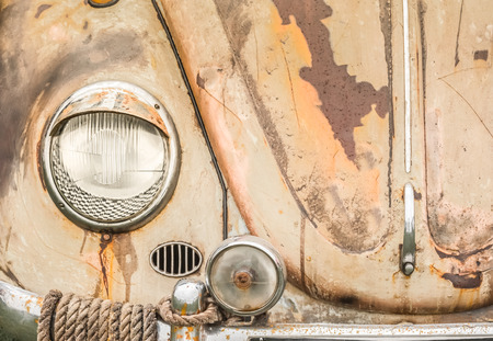 close-up of a vintage vehicle headlamp and rusting hood