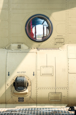 closeup of a military spec helicoper fusel;age and viewing window