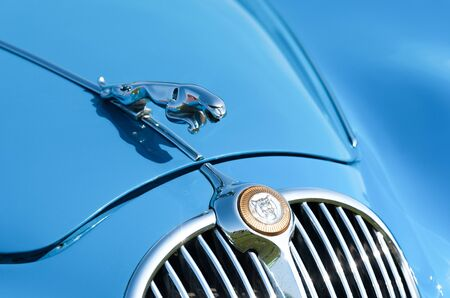 Vehicle badge and front grille closeup on a vintage Jaguar automobile in Rushmoor, UK - April 19, 2019
