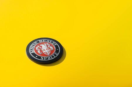 Vintage vehicle badge closeup on a yellow classic Austin Healey Sprite automobile - circa 1960 in Rushmoor, UK - April 19, 2019 Editorial