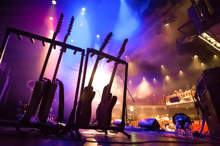 rack of electric guitars under stage lighting in a theatre