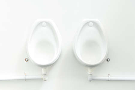 clean white public urinals fixed to a white wall Standard-Bild