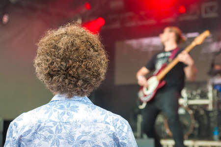 young person with very curly hair watching a rock band on stage Standard-Bild