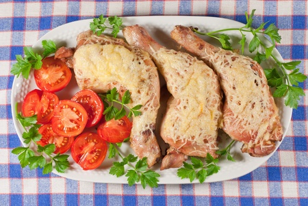 Fried chicken legs with cheese and tomato served on the white plate photo
