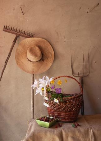 Stilleven van oud tuingereedschap, manden met bloemen en kersen Stockfoto