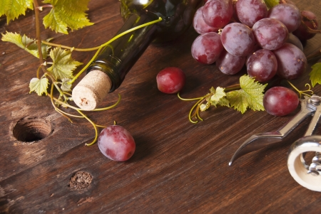Macro shot of grapes and bottle of wine on wooden board. Background photo