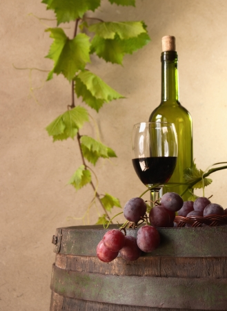 still life with red wine, bottle, glass and old barrel photo