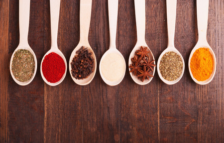 Various kind of spices in wooden bowls photo