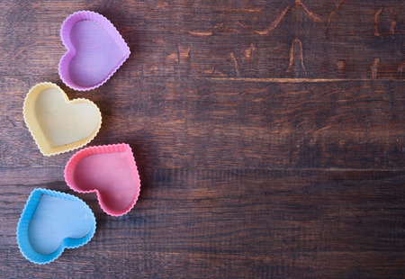 Heart Shaped Silicon Bun Cases on wooden background photo
