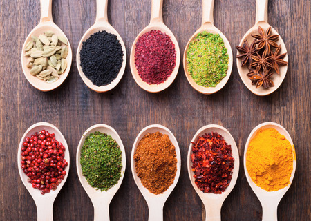 Assorted powder spices in wooden spoons on wood   Stock Photo