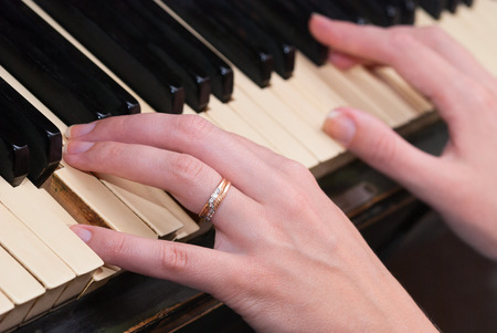 The hand on old piano keyboard photo