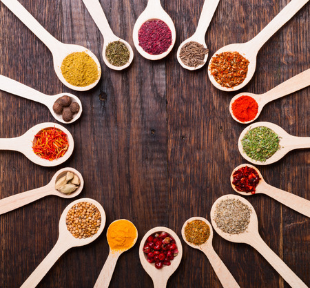Colorful spices in wooden spoons on wooden background photo