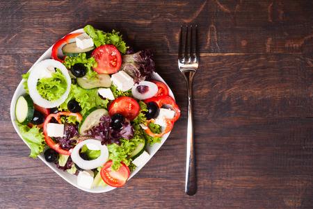 salad greens: Greek salad on wooden background