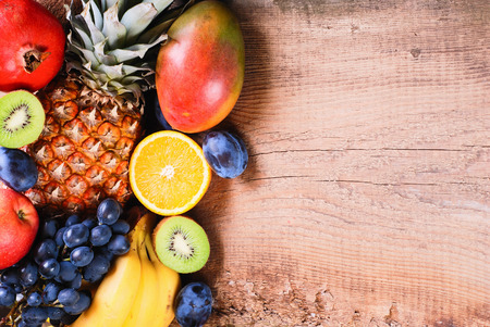 Many fresh colorful fruits on wooden backround photo