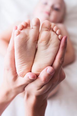 reflexologie plantaire: Jambe de l'enfant dans les mains bienveillantes du père