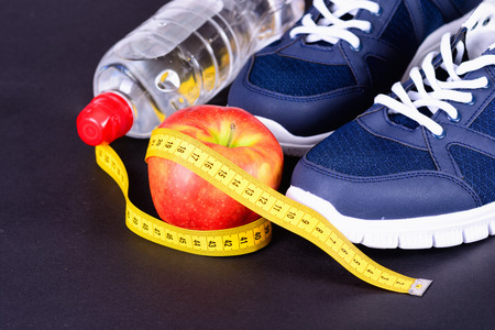 Fitness, weight loss concept with sneakers, apple & bottle Stock Photo