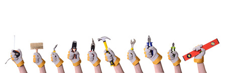 Tools in hand . Isolated on white background .