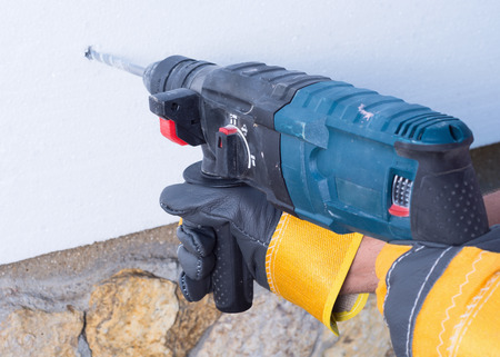 warms: worker  with rock-drill warms the wall